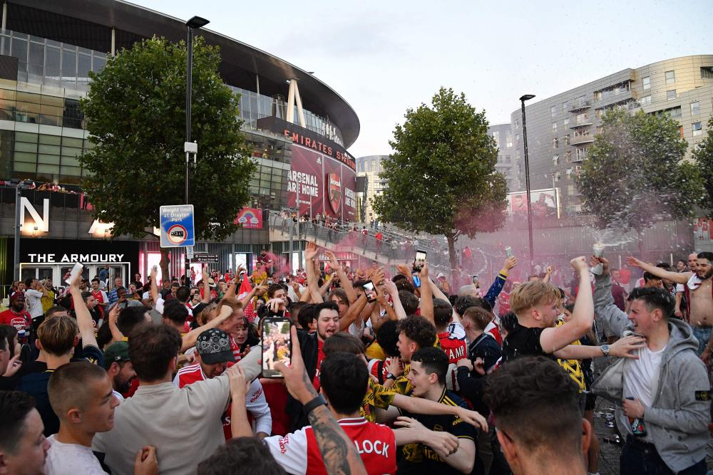 Arsenal fans celebrate outside the Emirates stadium.