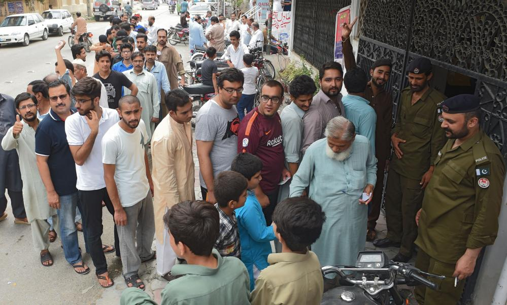 Pakistani voters lineup to cast their ballot outside a polling station in Rawalpindi