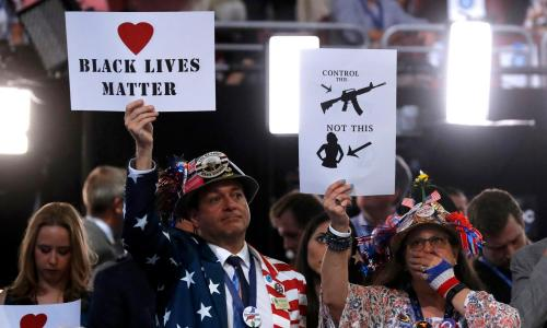 Delegates hold up signs during the second day at the Democratic national convention in Philadelphia, 26 July.
