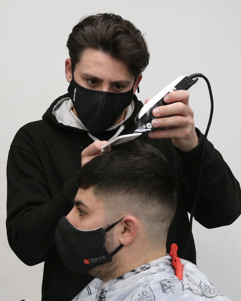 Barber Tony Mann trims Max Mann's hair at Tony Mann's Barber Shop in Giffnock near Glasgow.