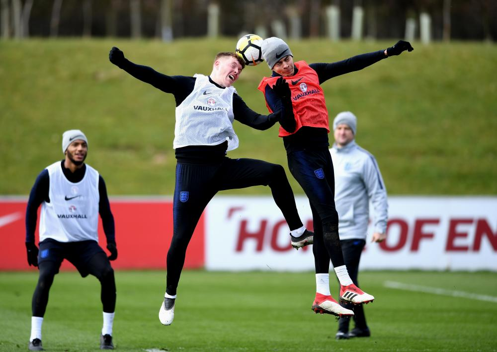 Alfie Mawson, left, and Dele Ali go up for a header during an England training session at St Georges Park.