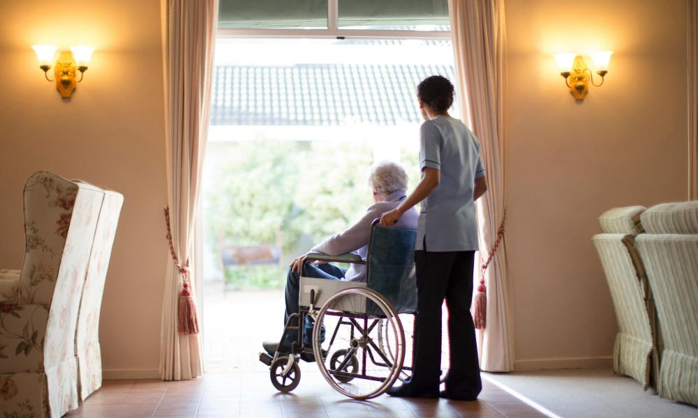 Nurse pushing patient in wheelchair.