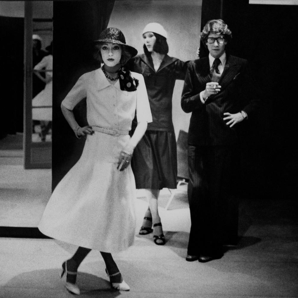 Yves Saint Laurent with De la Falaise (left) and his New York assistant, Marina Schiano, wearing his designs, for Vogue in 1975.