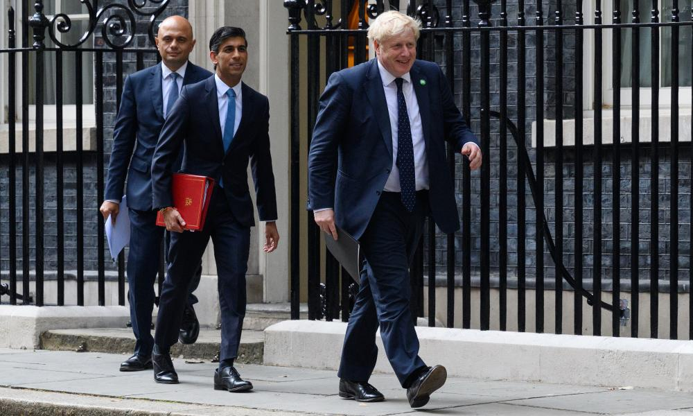 Sajid Javid (L), Rishi Sunak (C) and Boris Johnson (R) walks towards the door of number 9, Downing Street ahead of a press conference.