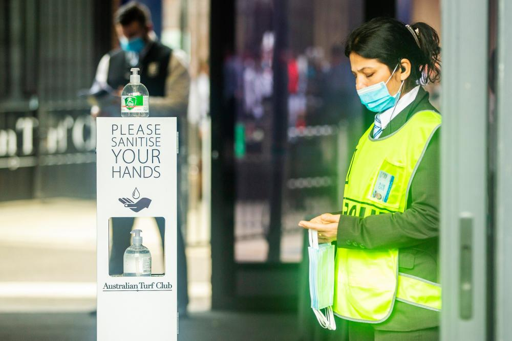 A security guard is seen holding masks at the entrance of Royal Randwick Racecourse in Sydney on Saturday. Crowd limits were increased for The Everest race day with almost 11,000 people allowed to attend following approval of Covid-safe plans submitted to the NSW government.