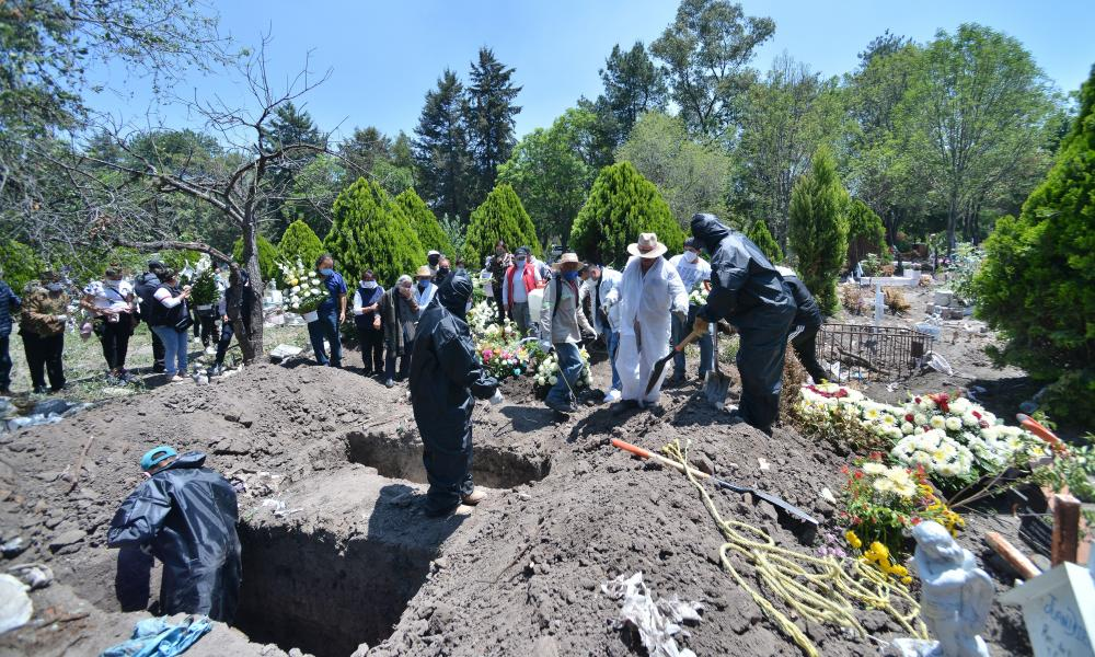 Cemetery workers wear protective gear while they place the plastic-wrapped coffin of a man who died from suspected coronavirus into a grave at San Isidro cemetery, Mexico City, Mexico, 15 Jun 2020.