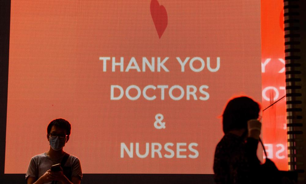 Pedestrians walk past an electronic display board with a message of thanks to doctors and nurses in Hong Kong on 13 May 2020.