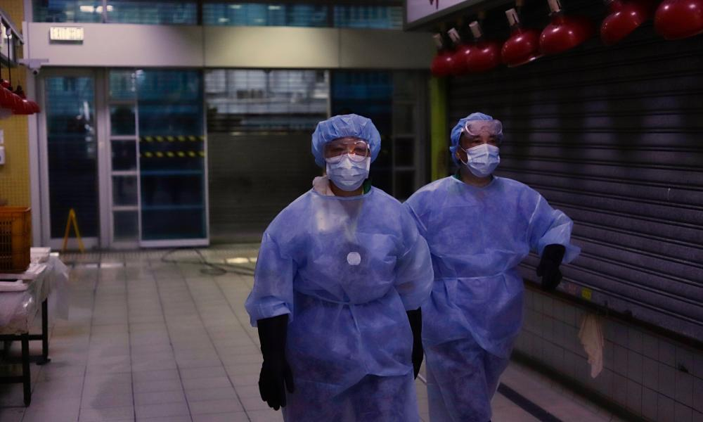 Janitors dressed in protective gear walk through an empty arcade in Hong Kong, 20 July 2020.