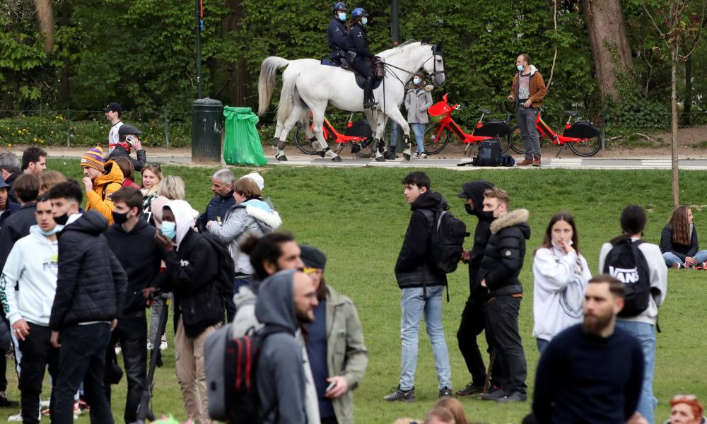 """Police officers ride horses next to people gathering at the Bois de la Cambre/Ter Kamerenbos park for a party called """"La Boum 2""""."""
