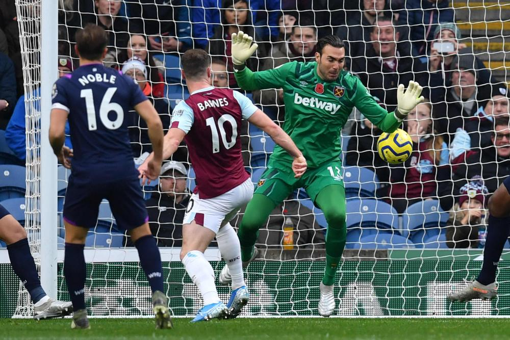 Burnley's Ashley Barnes prods the ball past West Ham United's goalkeeper Roberto to open the scoring.