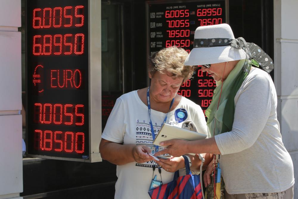 tourists count their turkish liras after exchanging foreign currency at a exchange shop in istanbul