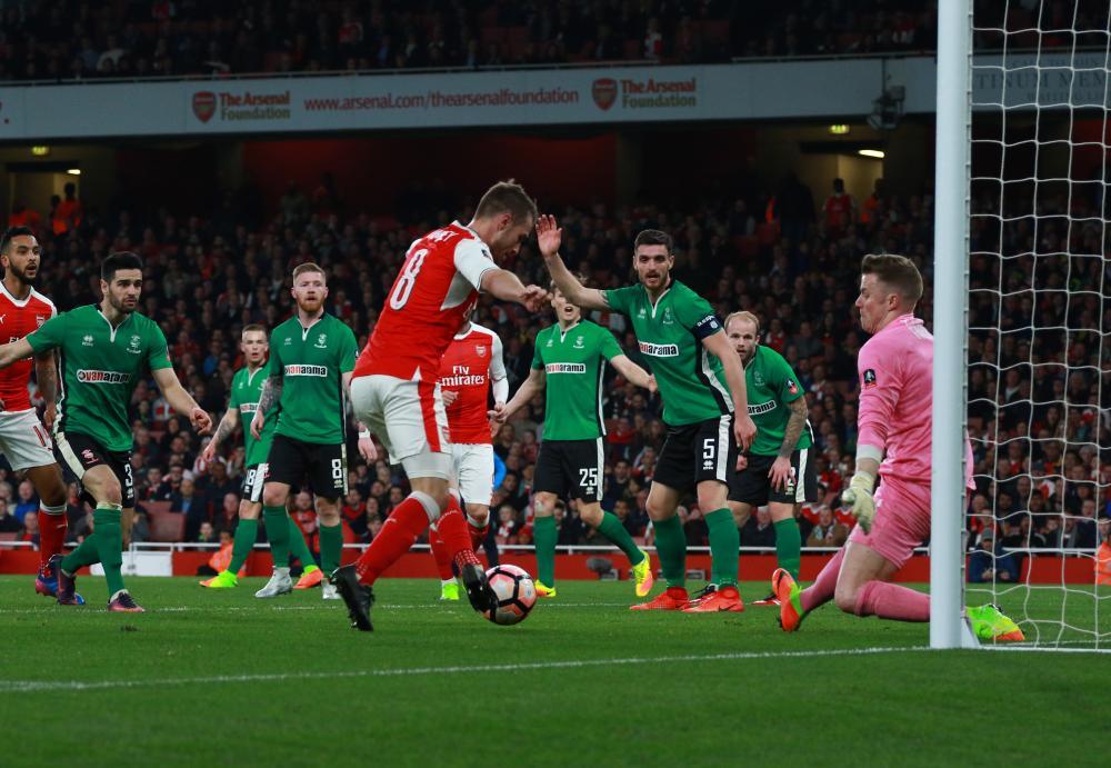 Aaron Ramsey jinks past Lincoln keeper Paul Farman to score Arsenal's fifth.