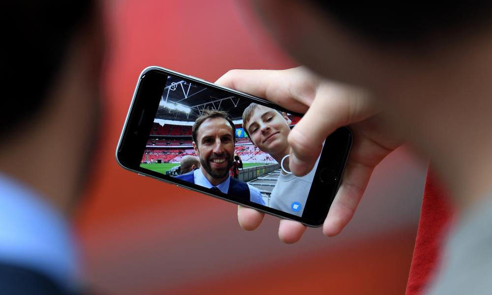 Spot the photographer: Gareth Southgate poses with a fan ahead of the game.