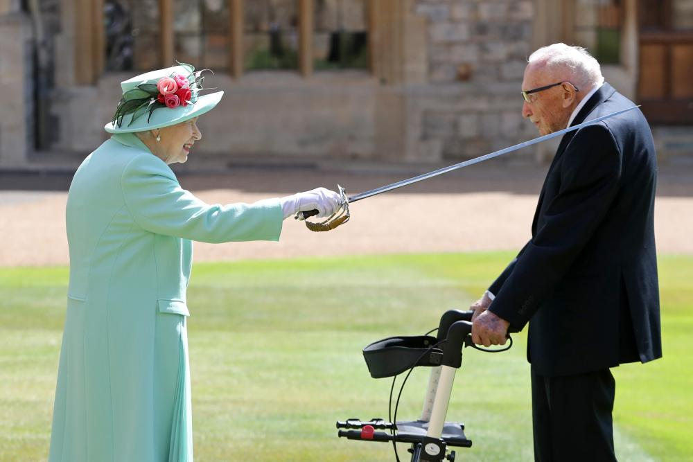 Queen Elizabeth II awards Captain Sir Thomas Moore with the insignia of Knight Bachelor at Windsor Castle in July.