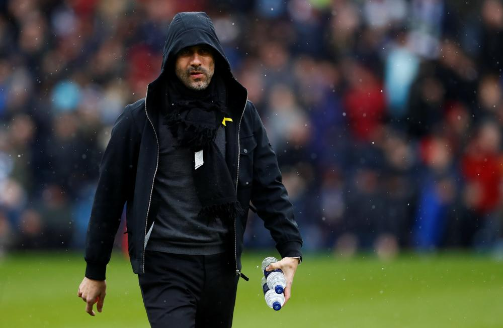 Pep Guardiola in the rain at Turf Moor.