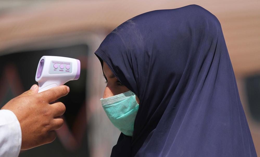 A health official checks the temperature of a woman in Herat.