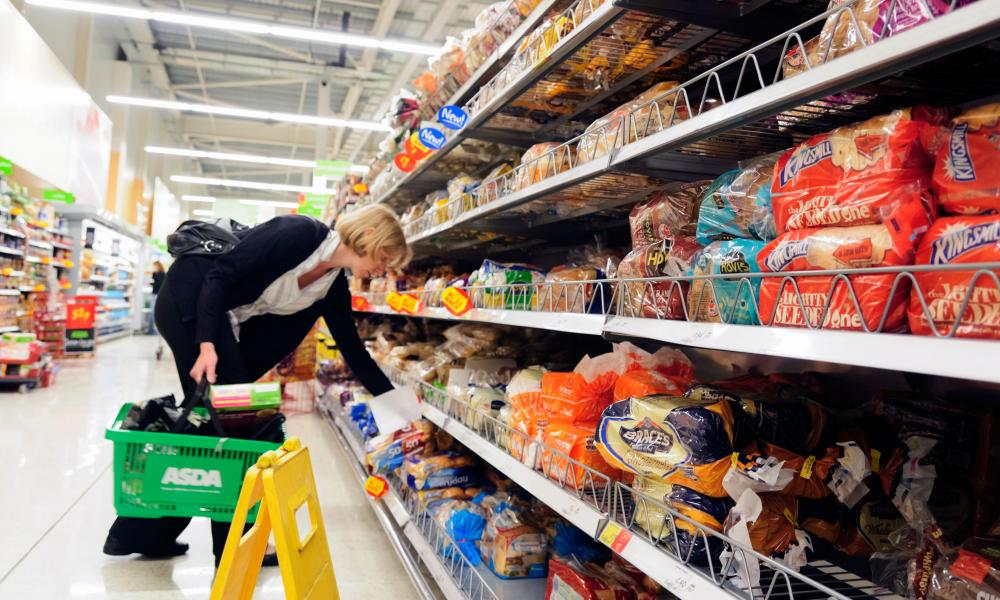 Woman buying bread in an Asda supermarket, England, UK