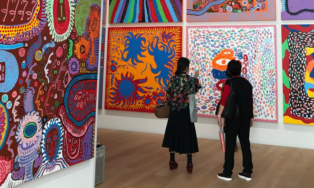 Visitors look at work by Kusama during a media preview of the exhibition