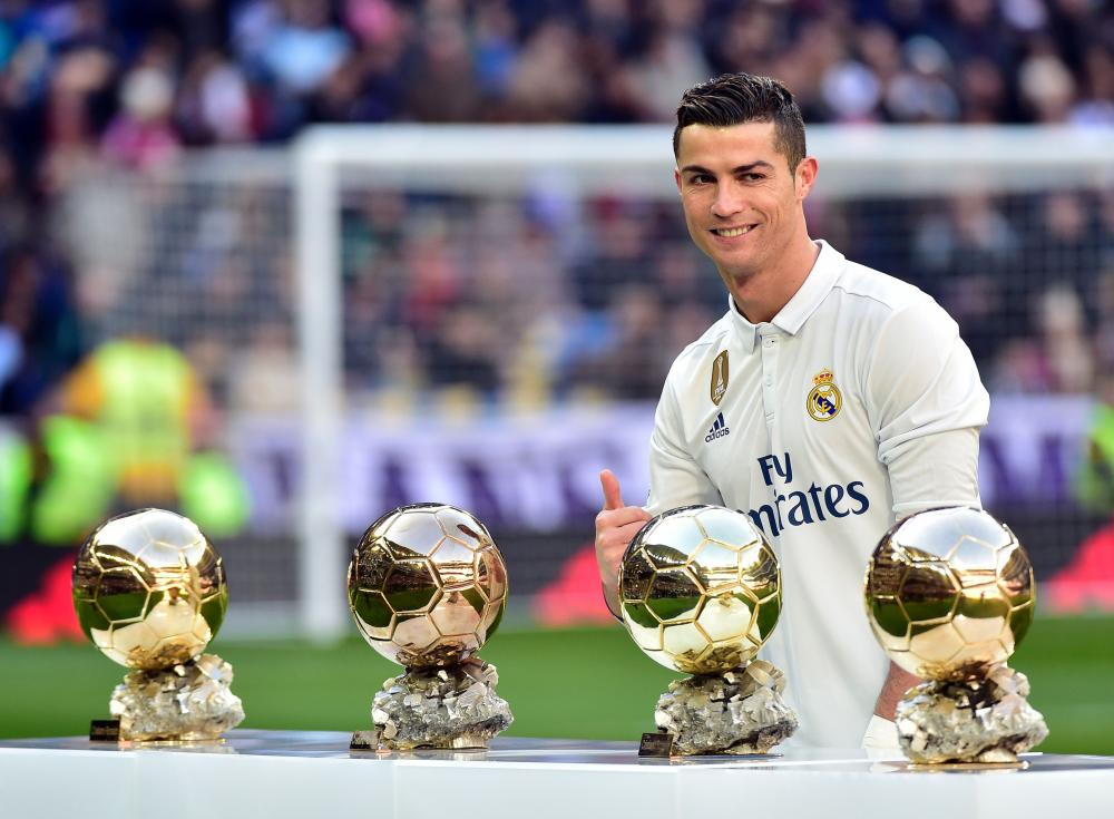 Cristiano Ronaldo poses with his four Ballon d'Or trophies before the match.