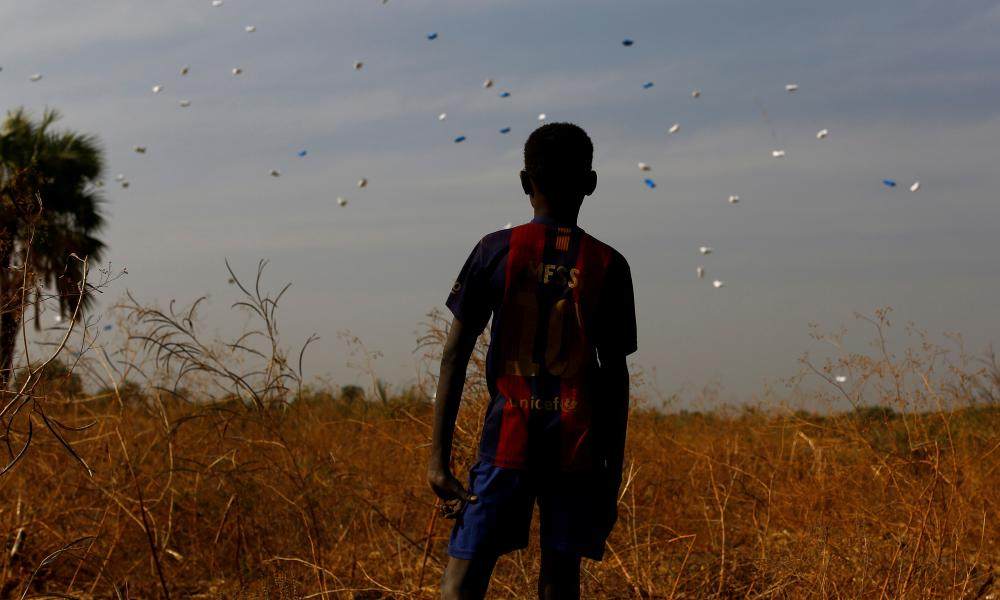 A boy watches sacks of food drop to the ground during a United Nations World Food Programme airdrop close to Rubkuai village in Unity State, northern South Sudan, in February 2017.