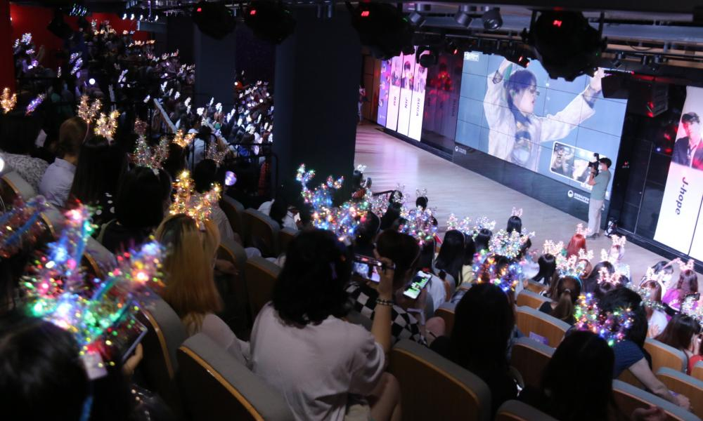 Fans of Chinese K-pop band BTS watch them perform at a Beijing festival in June