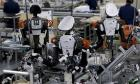 Humanoid robots work side by side with employees on the assembly line at a factory of Glory Ltd., in Kazo, Japan.