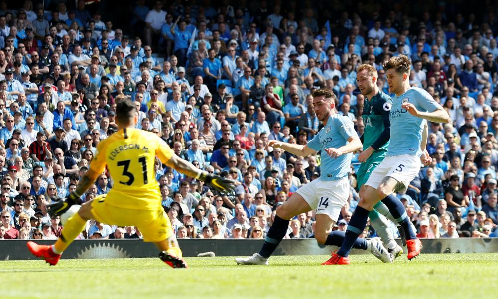 Manchester City's Ederson saves a shot from Tottenham's Christian Eriksen as Manchester City's John Stones and Aymeric Laporte look on.