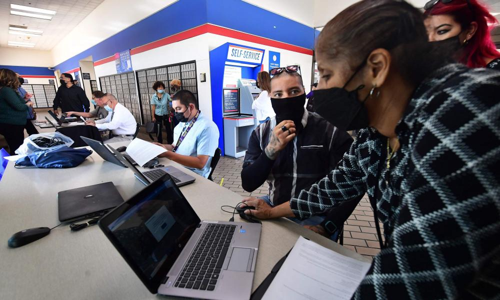 Melissa Honore-Madere of the US Postal Service helps applicant Andrew Valenzuela with his application during a job fair at a Post Office in Los Angeles, California on September 30, 2021.