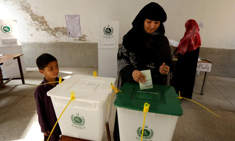 A child watches his mother casts her ballot at a polling station in Rawalpindi.