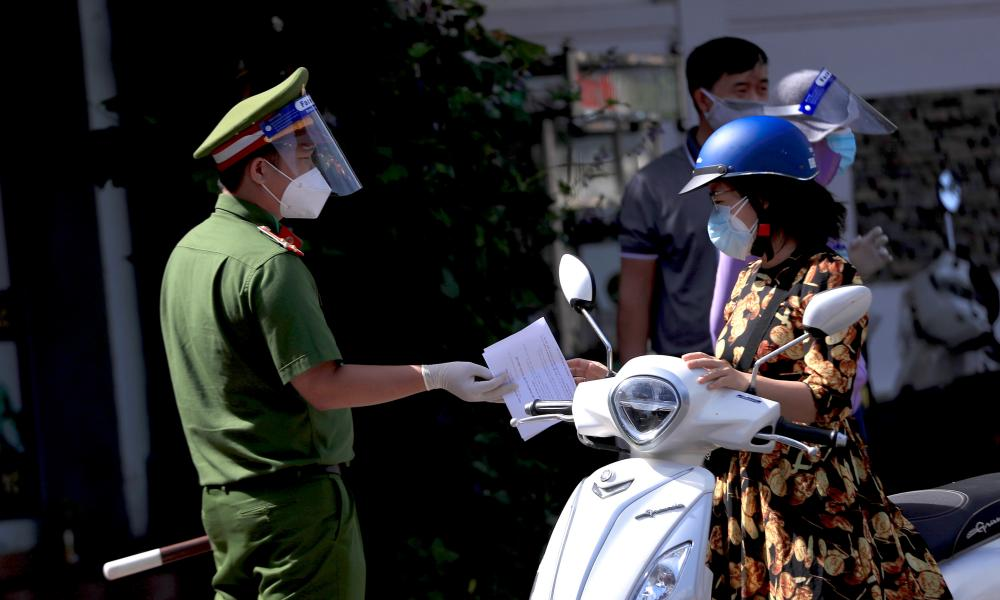 A policeman hands back a commuter's travel permit at a checkpoint in Vung Tau