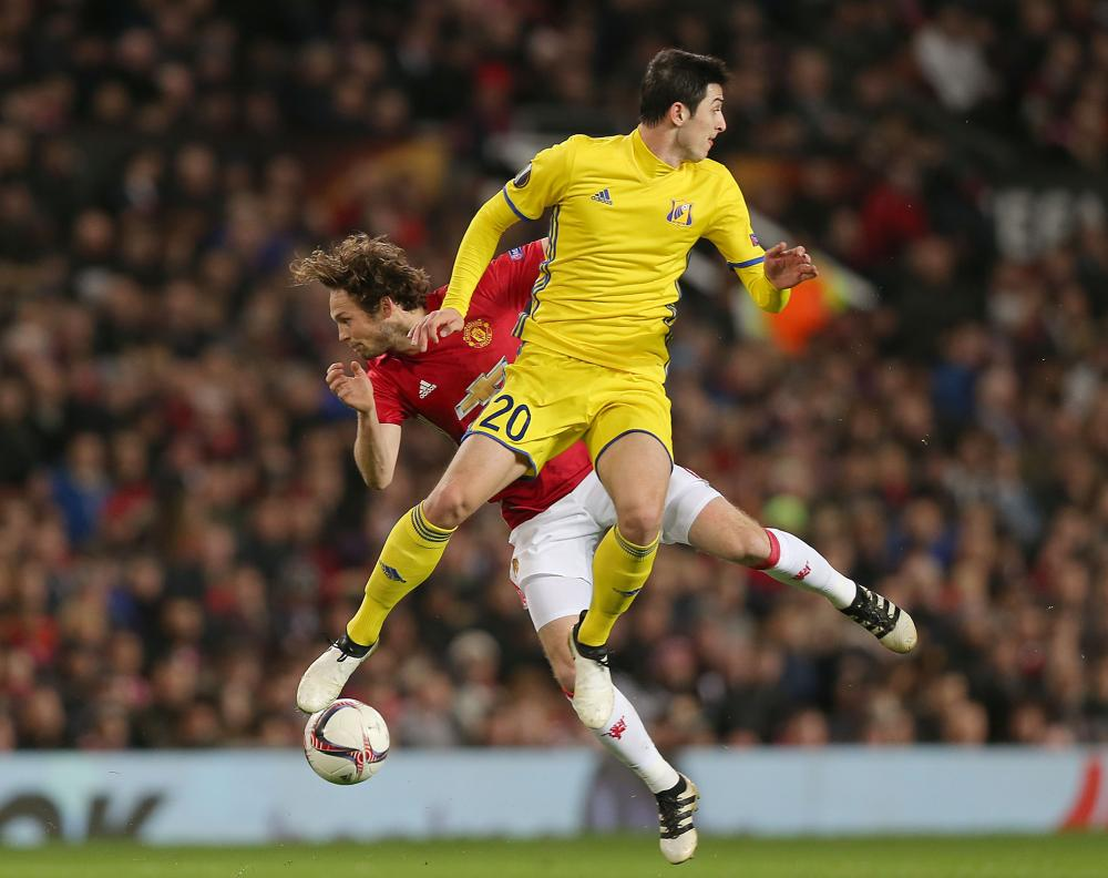 United's Daley Blind and Rostov's Sardar Azmoun tussle in the air.