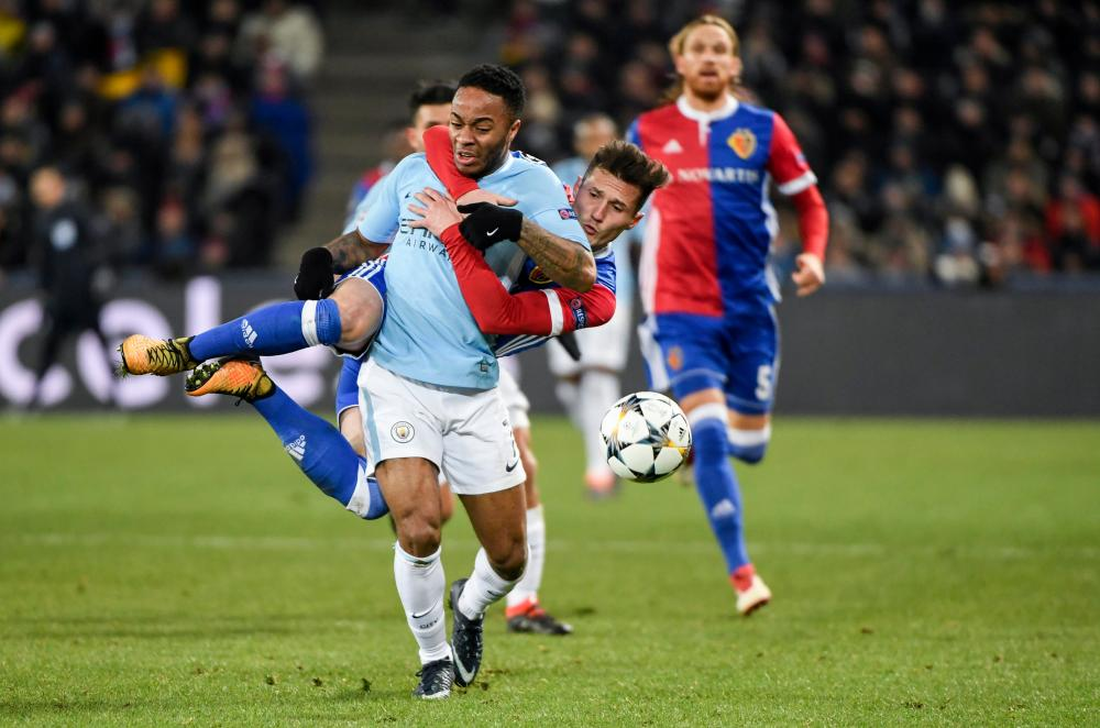 Basel's Taulant Xhaka attempts some sort of tackle against Raheem Sterling.