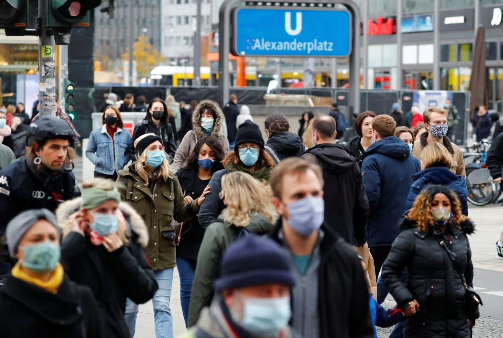 People wear protective face masks as they walk at Alexanderplatz shopping area in Berlin, Germany.