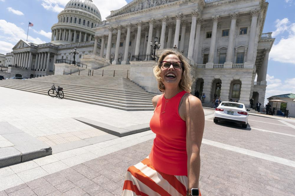 Kyrsten Sinema smiles as she returns to the Capitol after a meeting with  Joe Biden at the White House in Washington in June.