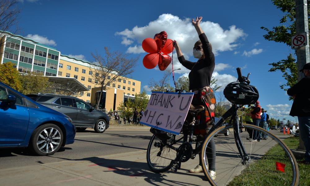 A woman waves balloons in support of healthcare workers treating Covid-19 patients outside the Royal Alexandra hospital in Edmonton, Alberta.
