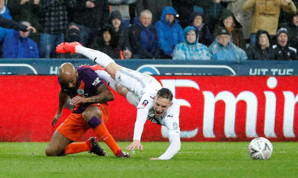 Swansea City's Connor Roberts is fouled by Manchester City's Fabian Delph resulting in a penalty being awarded.
