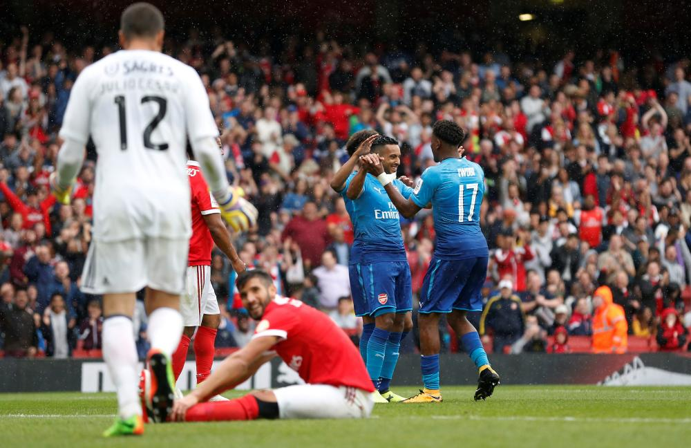Walcott and Iwobi celebrate after the third was scored by Benfica's Lisandro Lopez.