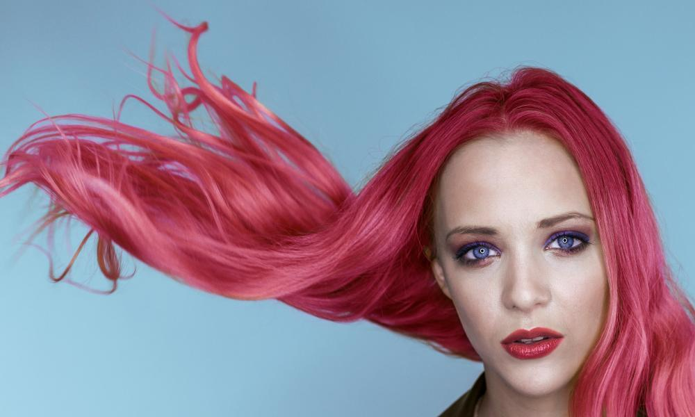 Woman with pink hair flying in the air