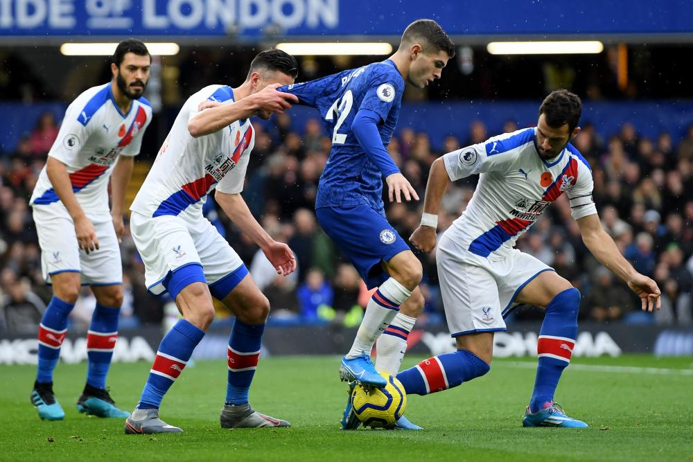 Christian Pulisic of Chelsea is challenged by James Tomkins, Sam Woods and Luka Milivojevic of Crystal Palace.