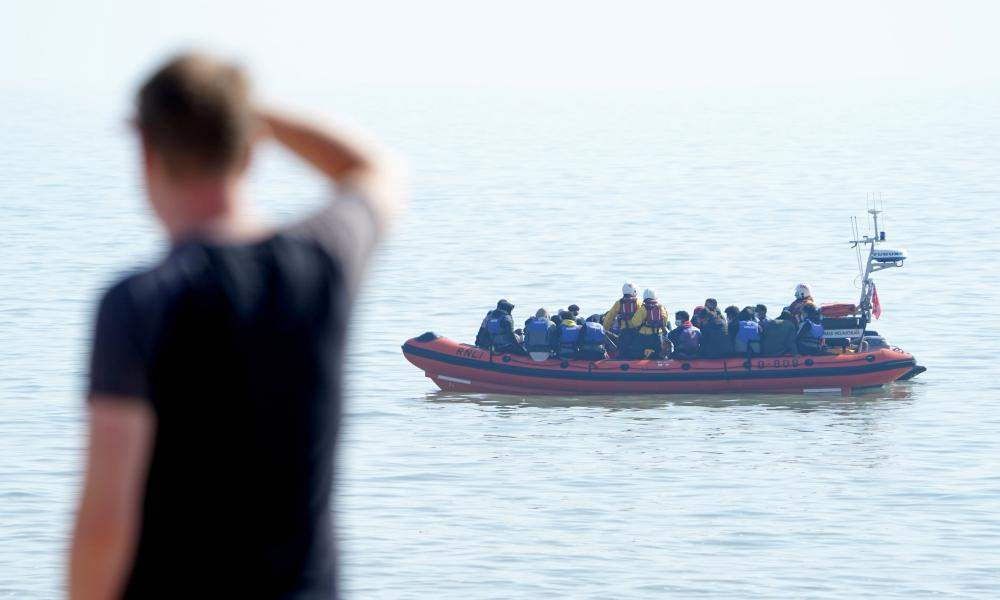 A man watches people thought to be migrants being brought to shore in Kent, after being intercepted by an RNLI crew.