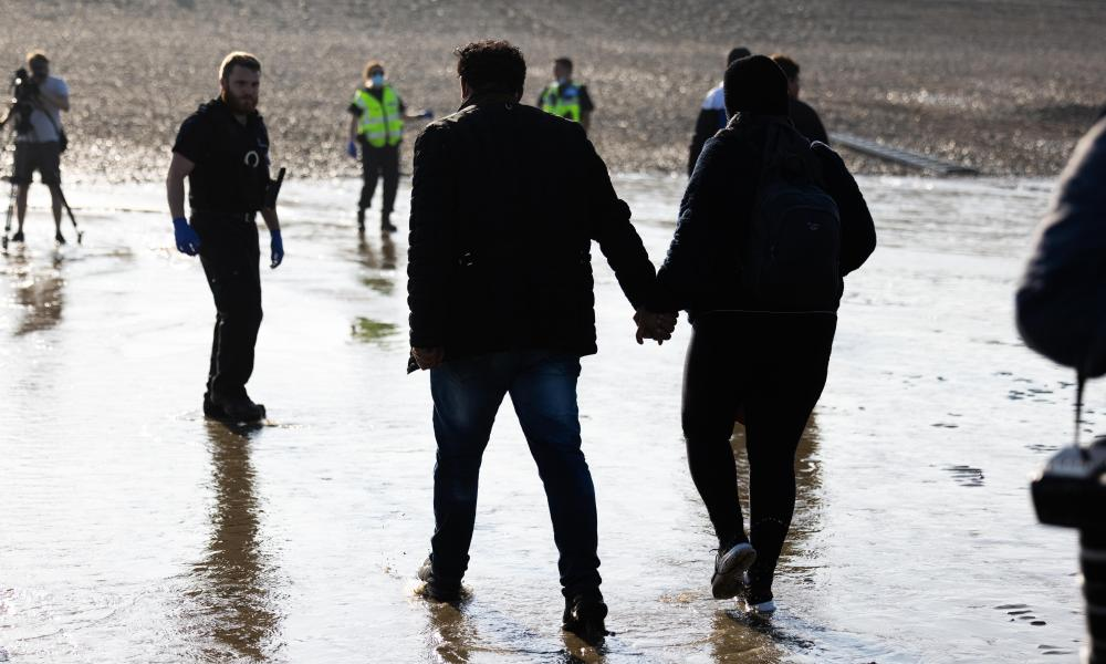 Two migrants hold hands as they make their way to shore to be processed by police.
