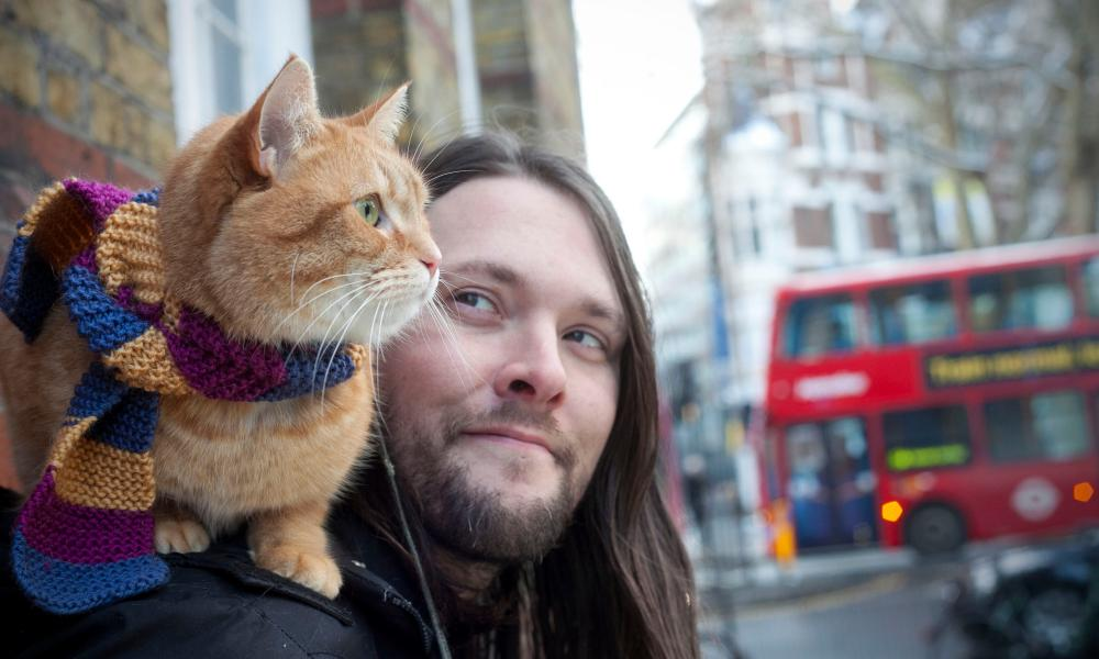 Portrait of James Bowen, a busker, with his cat Bob. Bowen hit the bestsellers with his book 'A Street Cat Named Bob', now he has written another book about Bob for children, Covent Garden, London, 21/01/2013 Sophia Evans for The Observer