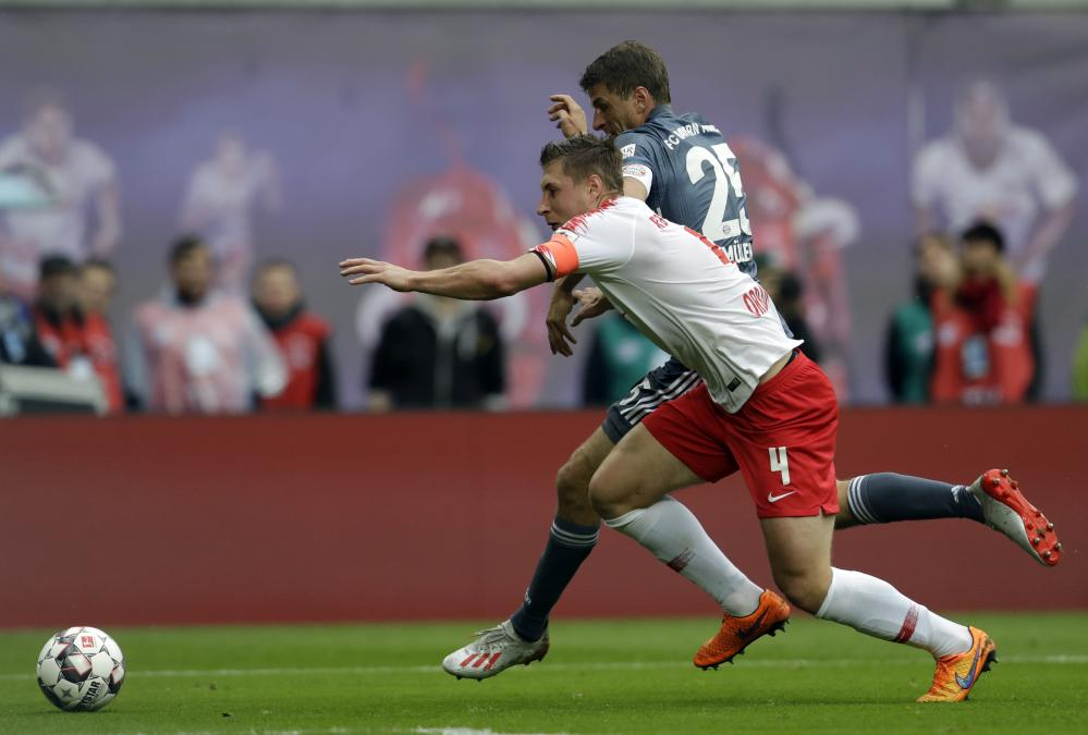 Leipzig's Willi Orban, front, fights for the ball with Bayern forward Thomas Müller.