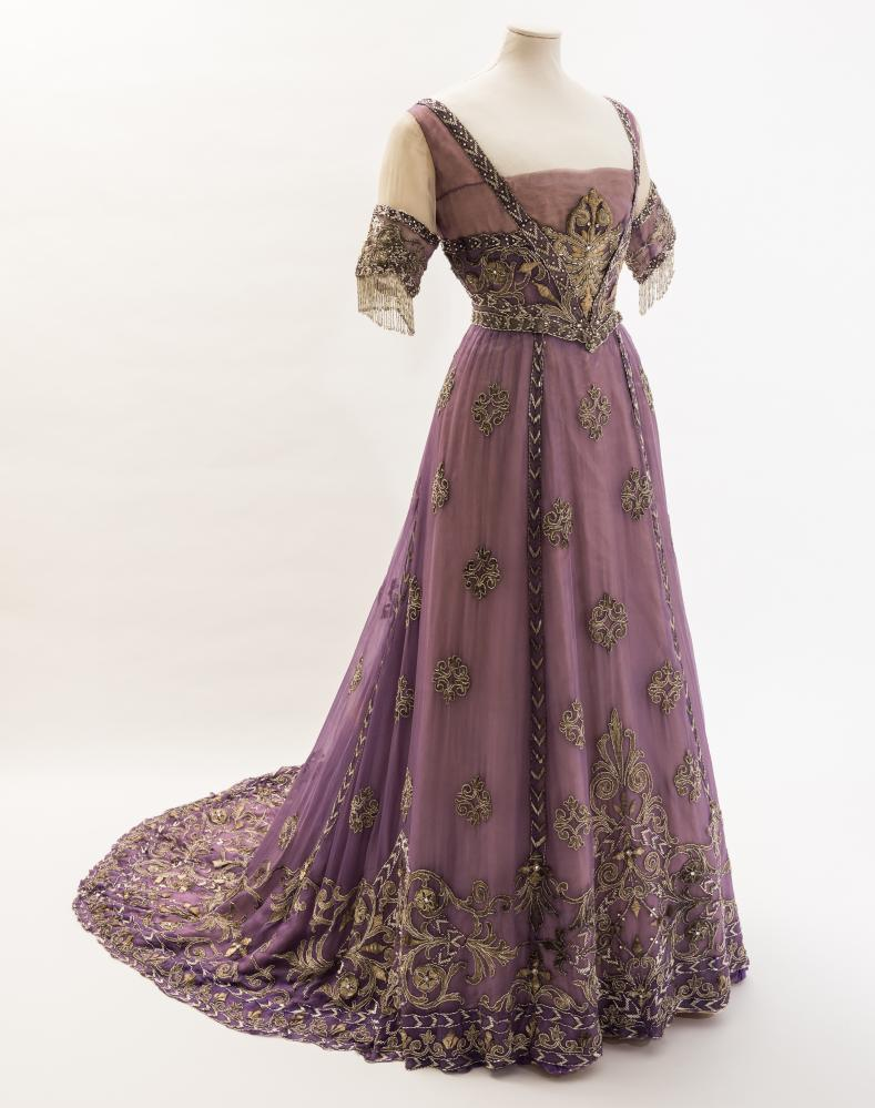 EVENING DRESS, embroidered chiffon by Doeuillet, Paris 1910 Purple silk chiffon evening dress with embroidered metal thread motifs, bugle beads and diamantés. Worn by Queen Alexandra