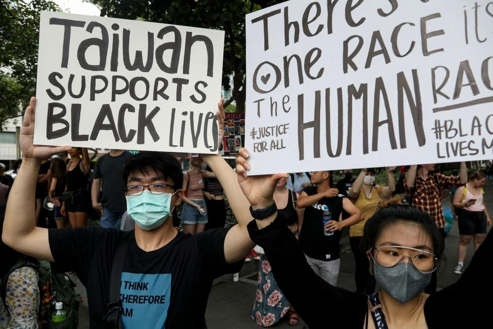 People hold posters supporting the Black Lives Matter movement in Taipei, Taiwan, June 13, 2020.