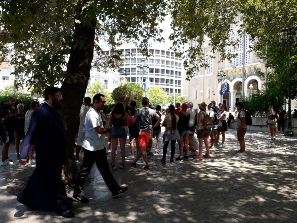 Holidaymakers listen to a tourist guide in front of Athens' cathedral.