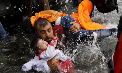 A Syrian refugee holds onto his children as he struggles to walk off a dinghy on the Greek island of Lesbos.