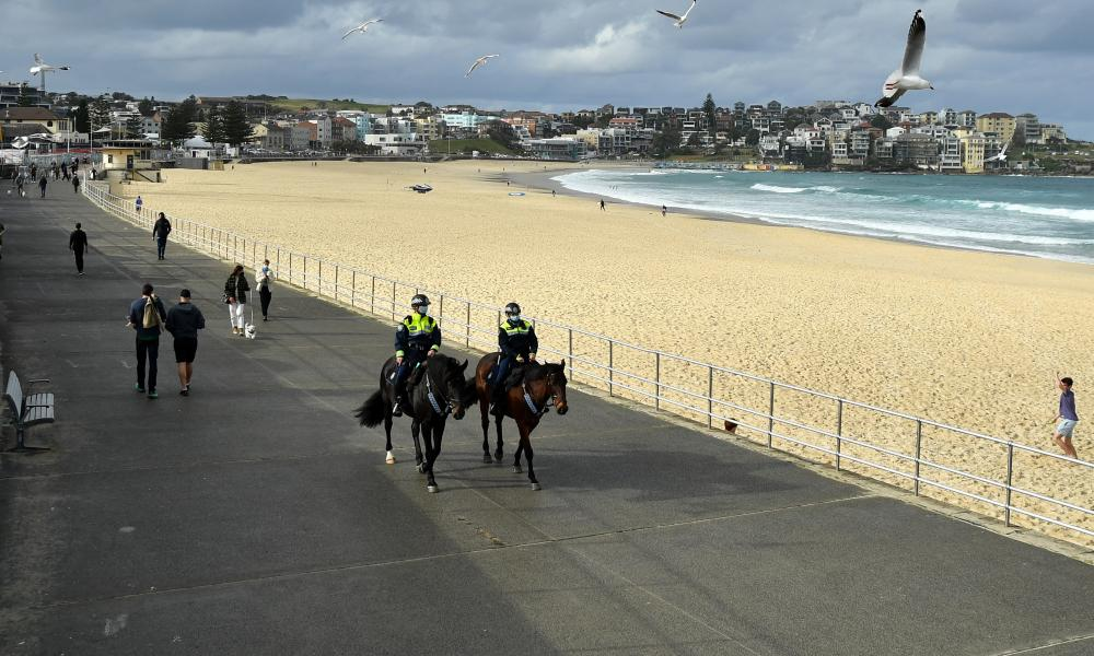Mounted police patrol Bondi Beach in Sydney, Australia on 28 June. With the entire state of NSW under Covid lockdown restrictions, check our full guide to the new and updated coronavirus rules around wearing face masks, home visitors, the 5km radius travel limit, and a curfew and one hour exercise time limit in the 12 LGAs of concern.