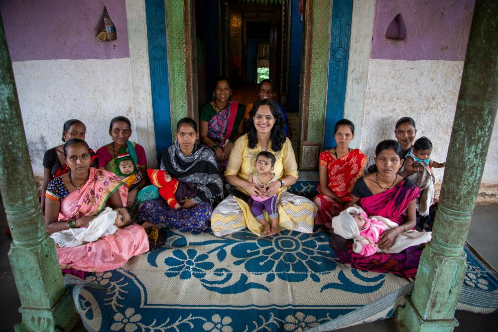Women sit in front of a doorway on a blue and white rug with babies and children in their laps