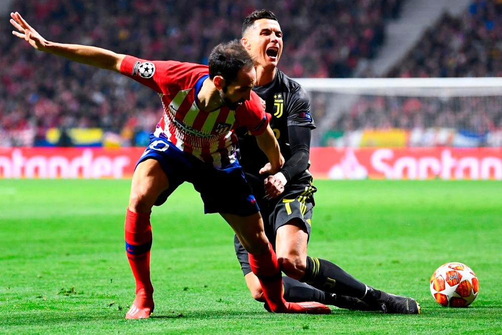 Juventus' Cristiano Ronaldo tussles with Atletico Madrid's Juanfran.
